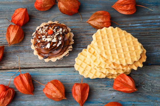 Sweet waffle cake with cream and physalis  on a  wooden background
