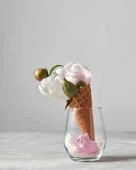 복사 공간이 있는 회색 배경에 유리 컵에 아름다운 흰색 모란 꽃과 꽃잎이 있는 달콤한 와플 콘. 발렌타인 데이 축하의 여름 개념