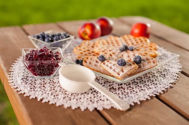 Сладкие вафли с фруктами в летний день на деревянном столе