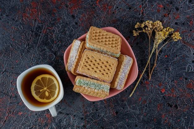 熱いお茶とミモザの花の白いカップと甘いワッフル