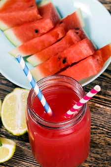 スイカとライムまたはレモンのかけらからの甘いスイカジュース、赤いジュースは自然で健康的で食事の多い製品であり、酸っぱいライムを含むスイカジュースです