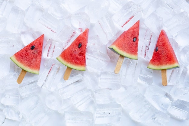 Sweet watermelon slice popsicles on ice background