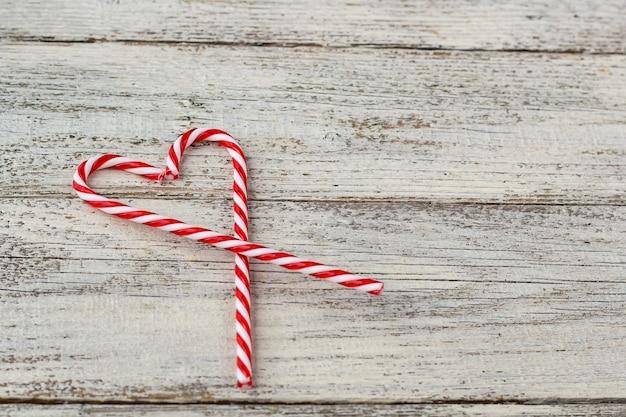 古い木製の背景にハートの形で甘い白と赤のキャンディケイン。クリスマス休暇またはバレンタインデーの概念