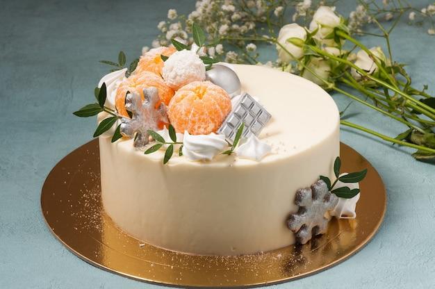 青い背景にみかんで飾られた甘いホワイトチョコレートケーキ。水平フレーム