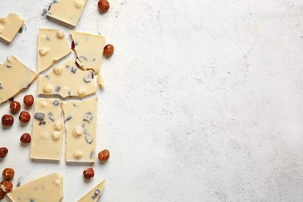 Сладкий белый шоколад с орехами на столе