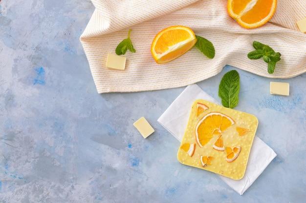 テーブルの上にオレンジと甘いホワイトチョコレート