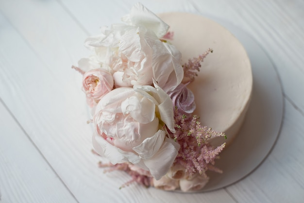 Sweet white cream cake round with pink roses flowers and white peony on top