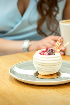 Sweet white cupcake with berries on the plate at the table on a woman's background with a cup of coffee in a cafe