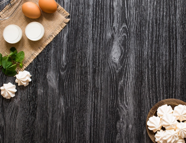 Sweet white meringue and other components on a wooden surface, free space for text.