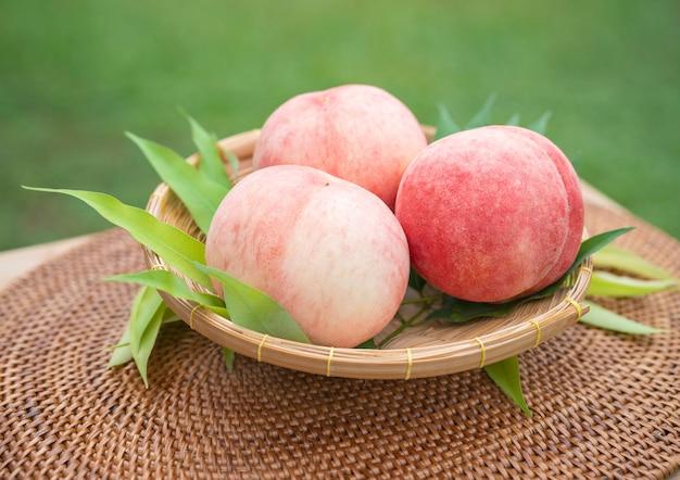 흐림 배경에서 달콤한 화이트 복숭아 과일, 정원에서 나무 테이블에 대나무 바구니에 신선한 흰 복숭아.
