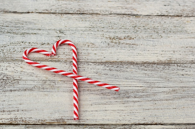 Sweet white and red candy canes in shape of heart on old wooden background. christmas holiday or valentine day concept