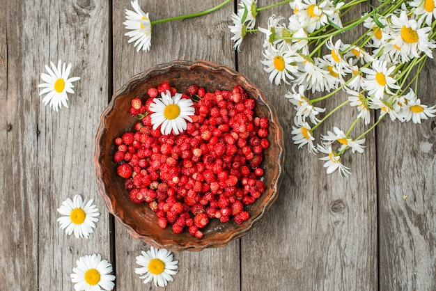 Sweet wild strawberries in plate with chamomile on wooden, top view.