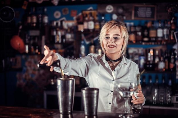 안경에 신선한 알코올 음료를 붓는 달콤한 여자 바텐더