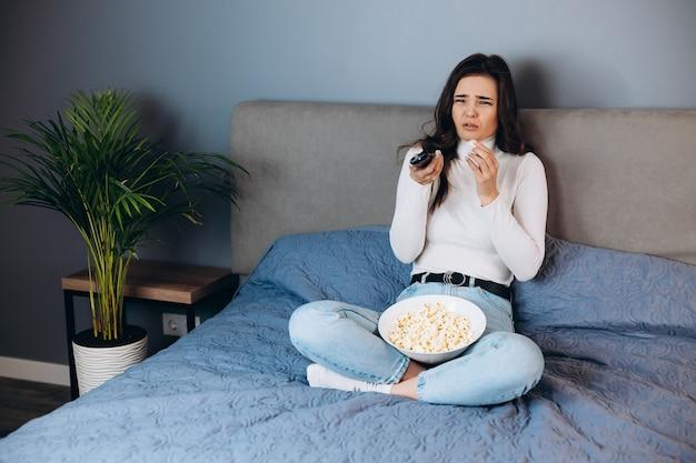 Милая женщина плачет и разочарована. симпатичная женщина в карантине, свободное время, смотреть фильм, впечатлена, удивлена неожиданным окончанием фильма / фильма, подержать большую коробку с попкорном, сидеть на диване в доме в помещении