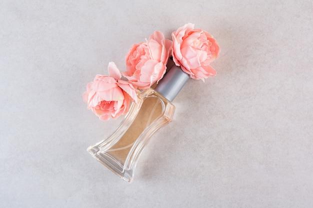 Sweet woman perfume with flowers on cream.