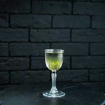 마티니와 보드카를 곁들인 달콤한 노랑-녹색 과일 시럽은 식당의 검은 나무 테이블에있는 테이블에 선다. 알코올 시음. 크리스탈 빈티지 유리에 맛있는 칵테일