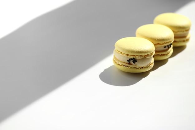 窓からの光線で白い背景に分離された甘い黄色のレモンフレンチマカロンまたはマカロンデザート。