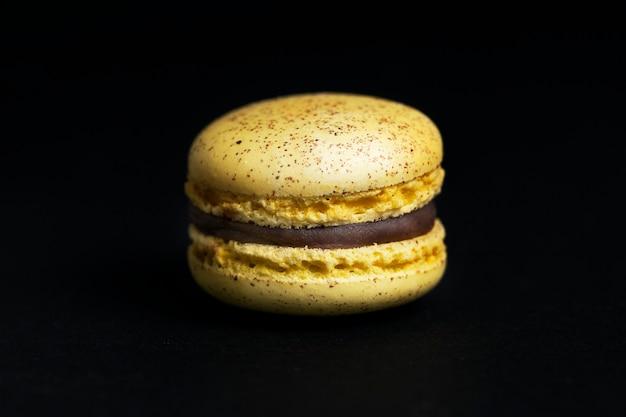 黒の背景に分離された甘い黄色いマカロン