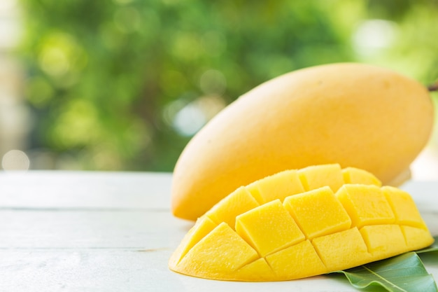 Sweet yellow mangos and slided on white wooden table on green nature