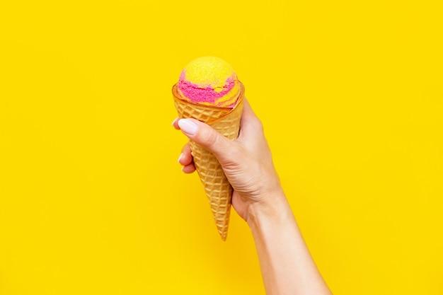 밝은 색상의 노란색 벽에 고립 된 여성 손에 바나나와 딸기 풍미와 와플 콘에 달콤한 노란색 분홍색 과일 아이스크림 셔벗