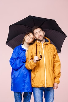 Sweet young beautiful couple posing in rain coats holding umbrella over light pink wall