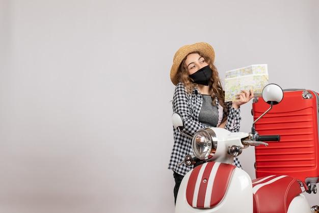 Dolce ragazza con maschera nera che tiene mappa in piedi vicino al motorino rosso