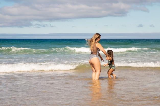 海のビーチで余暇を過ごして、海の水に足首を深く立っている甘い若いお母さんと小さな娘