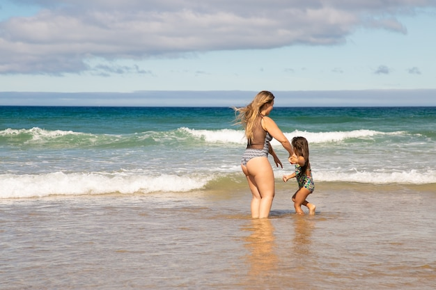 Sweet young mom and little daughter standing ankle deep in sea water, spending leisure time on beach at ocean