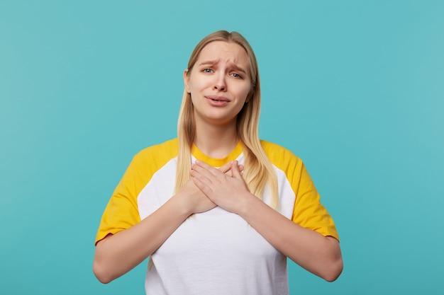 Dolce giovane bella donna bionda dai capelli lunghi con gli occhi azzurri che tiene i palmi sul petto mentre guarda emotivamente la fotocamera, indossando abiti casual mentre posa su sfondo blu