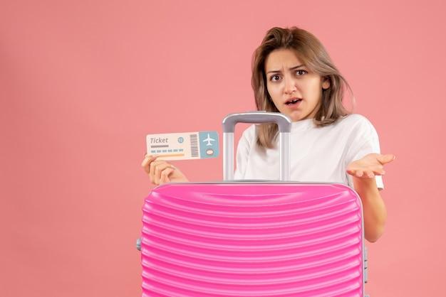 Dolce giovane donna che tiene il biglietto dietro la valigia rosa