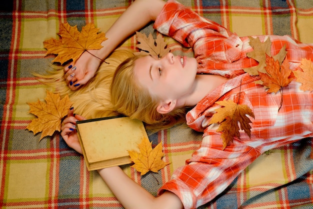 Sweet young woman playing with leaves and looks very sensually. happy young woman preparing for autumn sunny day. attractive young woman wearing in fashionable seasonal clothes having autumnal mood.
