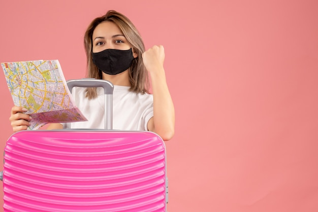 ピンクのスーツケースの後ろに地図を保持している黒いマスクを持つ甘い若い女性