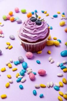 ライラックの背景にさまざまな色とりどりの砂糖ドラジェキャンディーの中に置かれたクリームとベリーの甘いおいしいブルーベリーカップケーキ