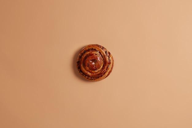 Dolce gustoso panino vorticoso alla cannella appena sfornato per il tuo spuntino o colazione. torta di sfoglia appetitosa malsana su fondo beige. concetto di pasticceria e panetteria. rotolo francese delizioso intero