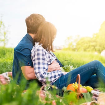 フィールド上のピクニックで素敵な時間を過ごしている恋人
