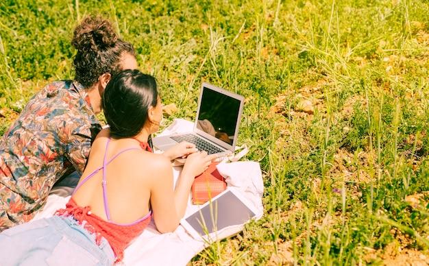 Sweethearts using laptop in field