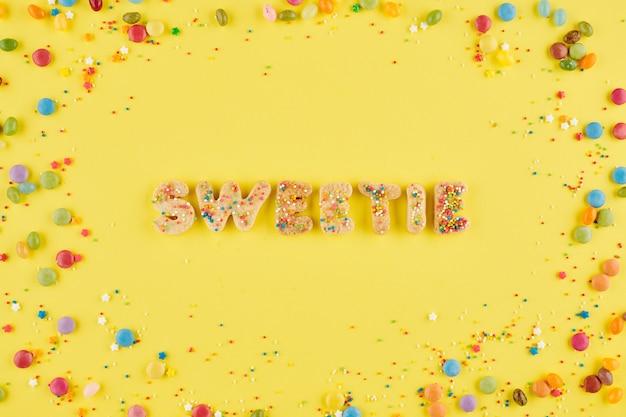 주위에 뿌리와 사탕이있는 구운 쿠키 편지에서 달콤한 단어