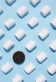 青いテーブル背景に甘いマシュマロ。