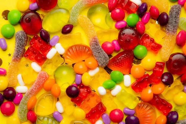 甘さの背景。キャンディー盛り合わせレイアウト。黄ピンクの背景にキャンディーとレイアウト。歯ごたえのあるマーマレードと小さなキャラメル。明るい背景。あらゆる好みのスイーツ。お菓子についての記事。