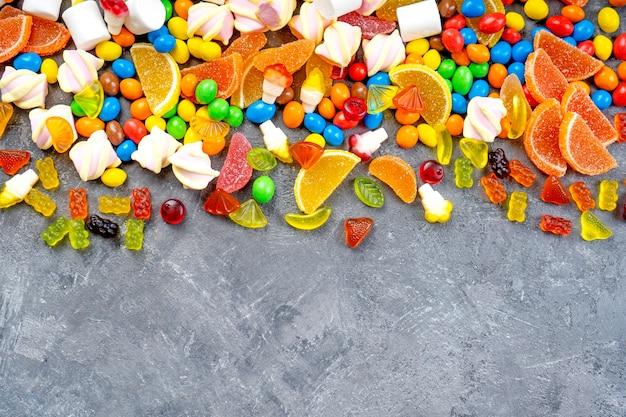 お菓子やキャンディーの背景。さまざまなキャンディー、マシュマロ、マーマレード、ユミグミがテーブルに散らばっています。上面図。