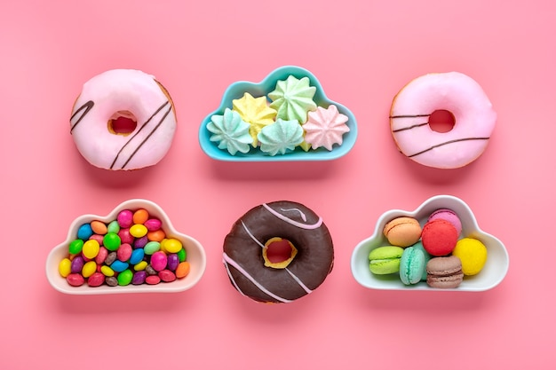 雲の形をしたボウルにスイーツとメレンゲ、カラフルなトッピングとピンクのドーナツとチョコレート