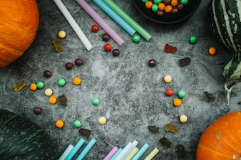 Sweets and straws near pumpkins