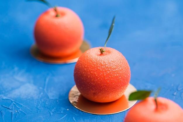 Сладости, торт и вкусная концепция - мусс-десерт в форме апельсинового фрукта.
