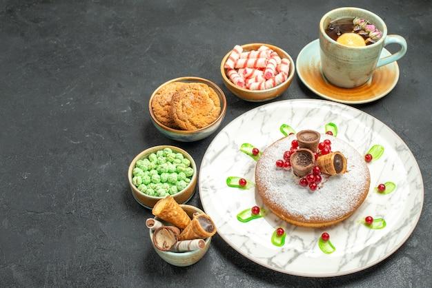 Torta di dolci con frutti di bosco una tazza di tè biscotti dolci cialde