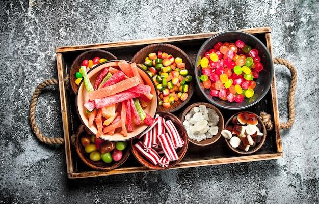 スイーツキャンディー、マシュマロとゼリーの砂糖漬けの果物を木製のトレイに載せたもの。素朴な背景に。