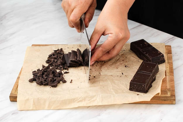 Sweets, confectionery and culinary concept - female hands with kitchen knife chopping chocolate bar to chips on wooden board on white  background