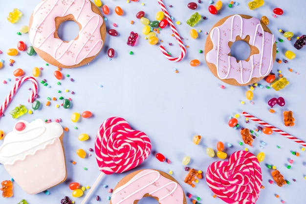 Sweets creative lay out, dessert concept with lollipops, jellies, candy, cookies donuts and cupcakes, light blue background