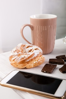 Sweets and cup of coffee closeup. mobile phone on wooden table, morning breakfast concept