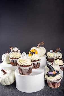할로윈 파티를 위한 과자. 현대적인 스탠드에 있는 재미있는 홈메이드 할로윈 컵케이크와 어두운 배경의 연단. 할로윈 파티 취급 개념