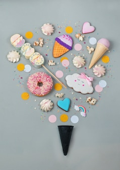Sweets in ice cream shape with black waffle cone on grey background